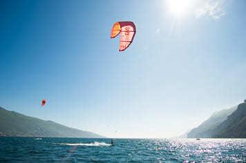 Ein Kitesurfer überquert den Gardasee