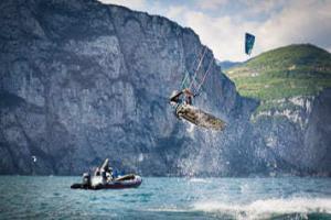 Ein Kitesurfer springt vor einem Boot