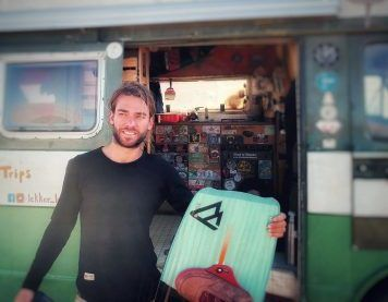 Dany mit einem Kiteboard vor seinem Van