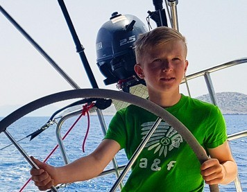 Praktikant von Avid Kiteboarding am Steuer eines Segelbootes