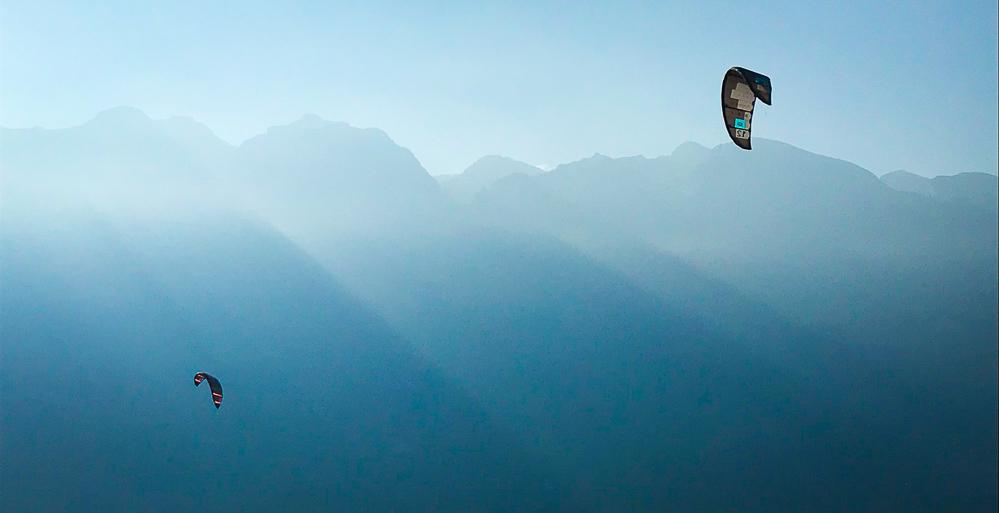 Kites fliegen im Wind vor Bergen