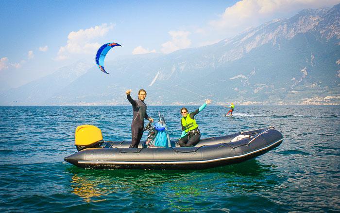 Ein Kitesurfer fährt hinter dem Schulungsboot während der Praxissession